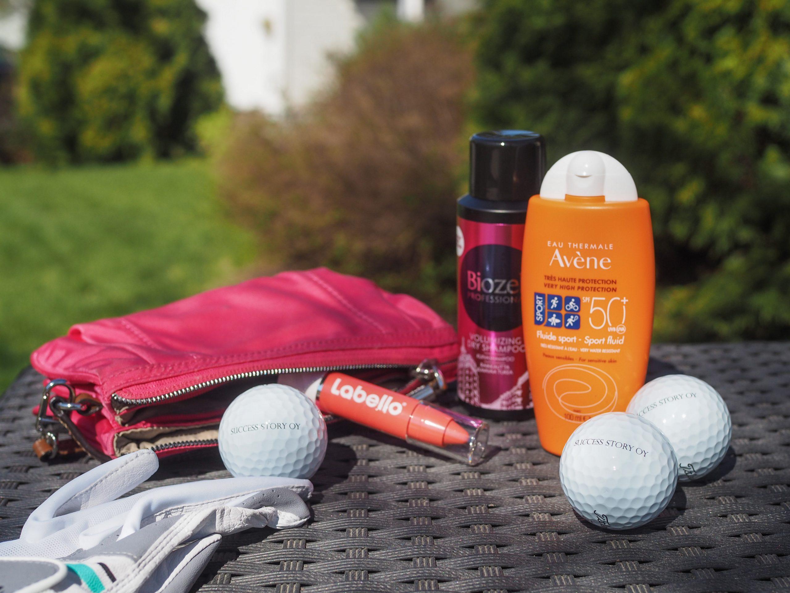 Avene-aurinkovoide, Biozell-kuivashampoo ja Labello-huulipuna sekä golfhanska ja golfpalloja pöydällä