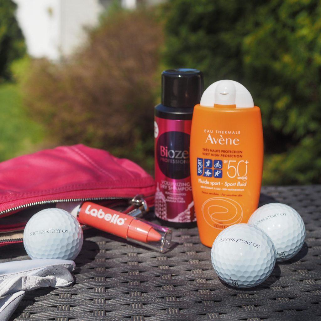 Avene -aurinkovoide, Biozell-kuivashampoo, Labello-huulipuna sekä golfpalloja pöydällä