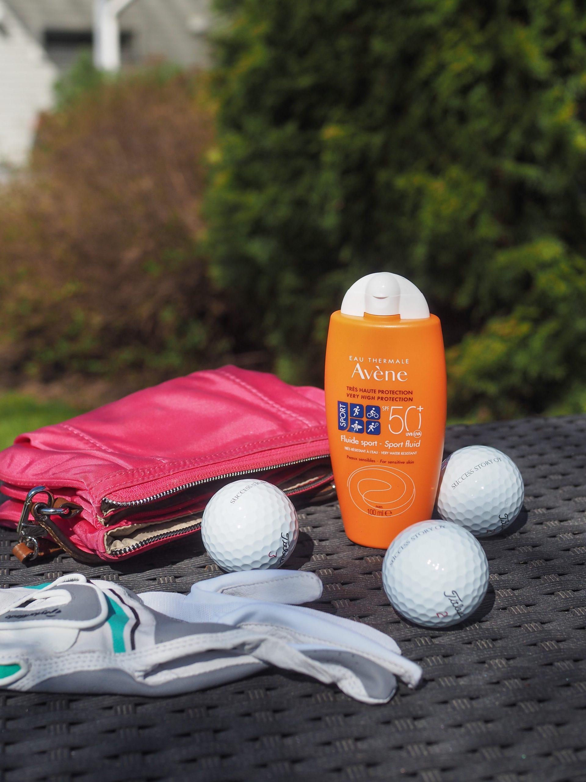 Avene Sun Sport -aurinkovoide, golfhanska ja golfpalloja pöydällä
