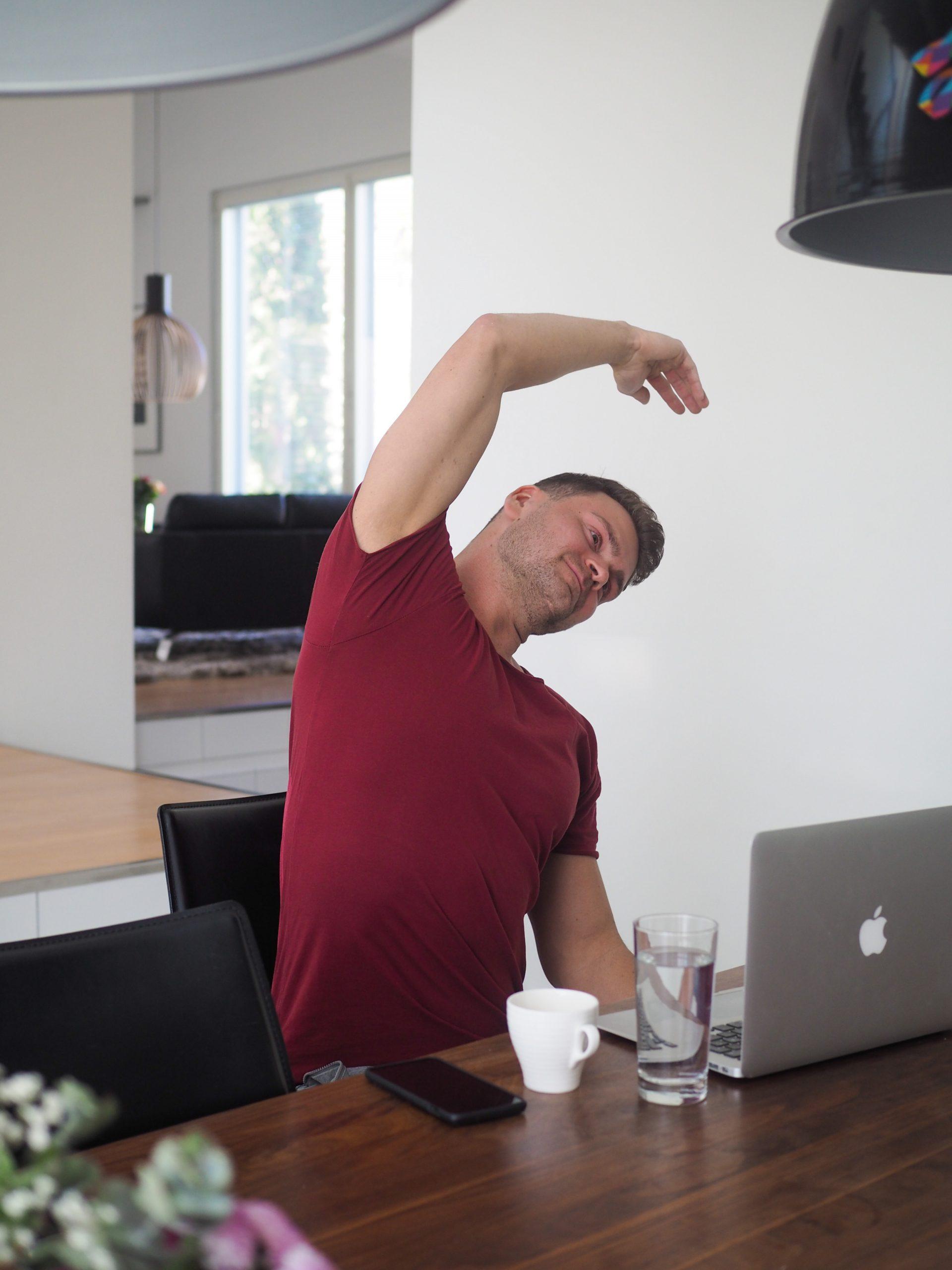 Mies punaisessa paidassa taukojumppaa, kyljen venytys