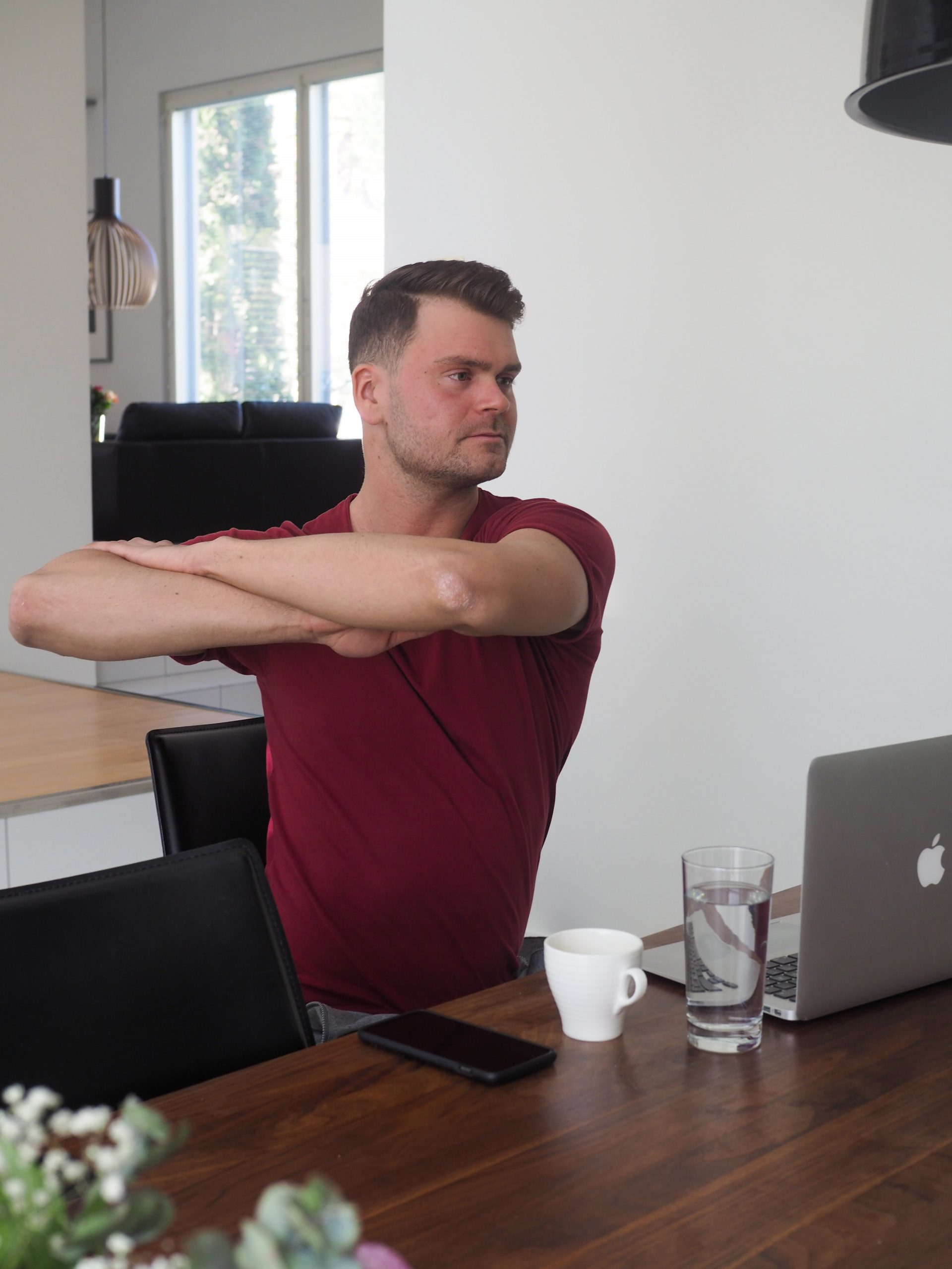 Mies punaisessa paidassa tekee taukojumppaa, vartalon kierto istuen