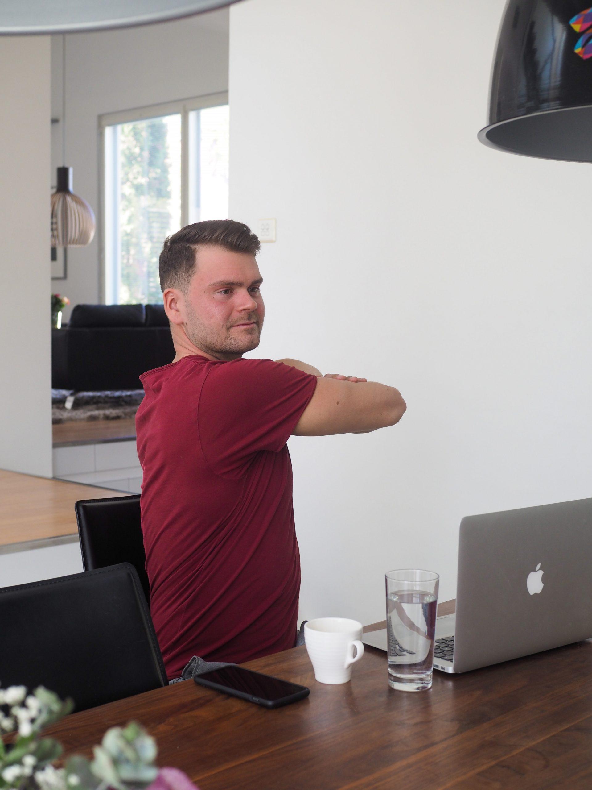 Mies punaisessa paidassa taukojumppaa, vartalon kierto istuen