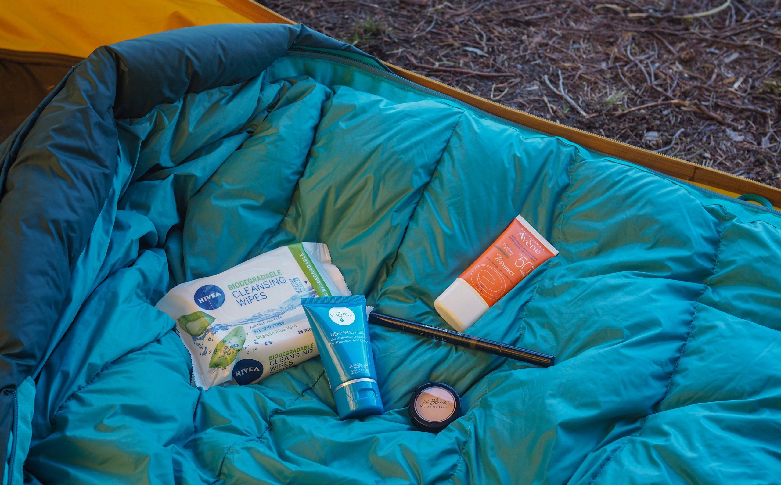 Kosmetiikkatuotteita teltassa makuupussin päällä