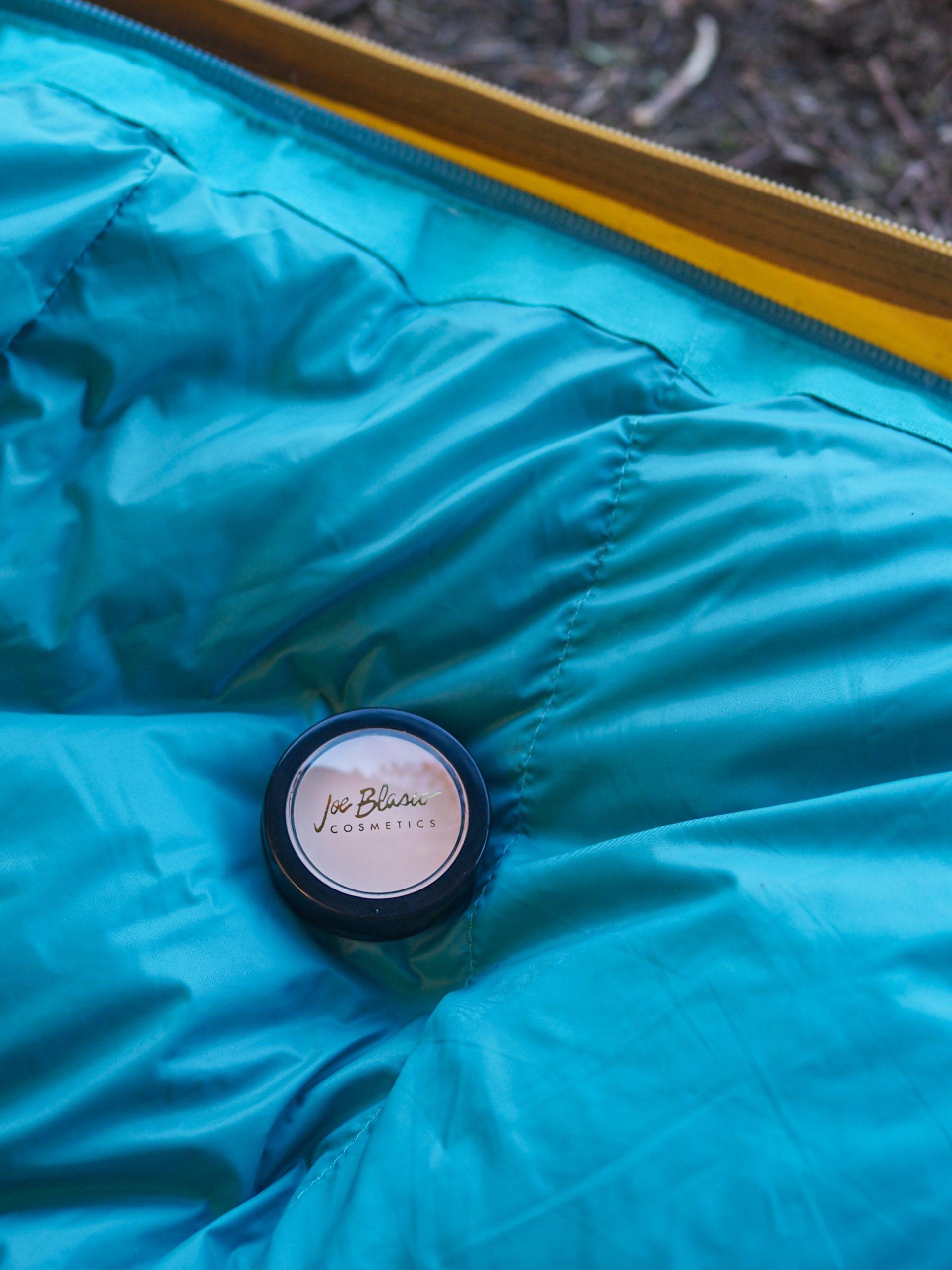 Joe Blascon peitevoide makuupussin päällä teltassa