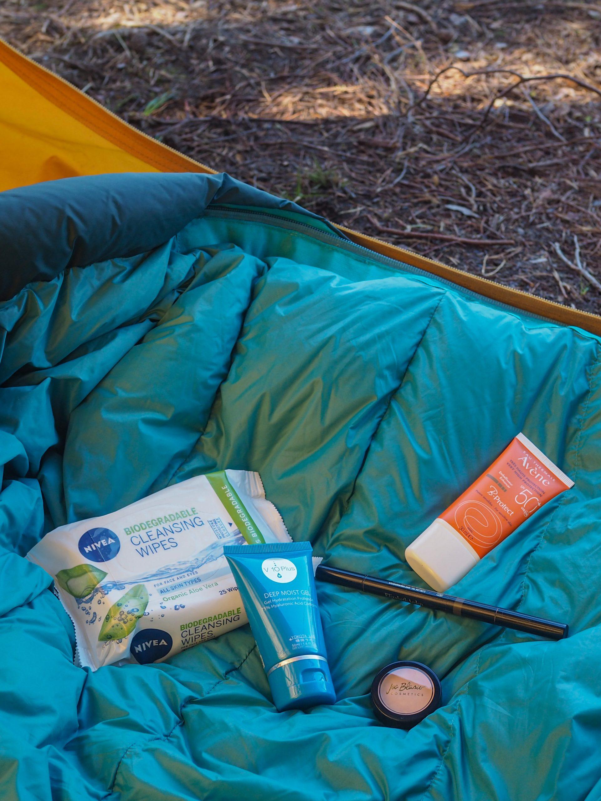 Puhdistusliinat, kosteusvoide, kulmakynä, peitevoide ja aurinkovoide makuupussin päällä teltassa