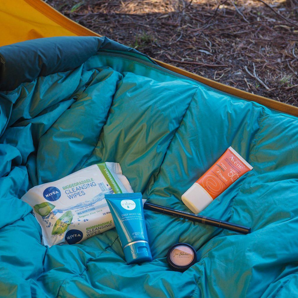 Puhdistusliinat, kosteusvoide, kulmakynä, peitevoide ja aurinkovoide teltassa makuupussin päällä