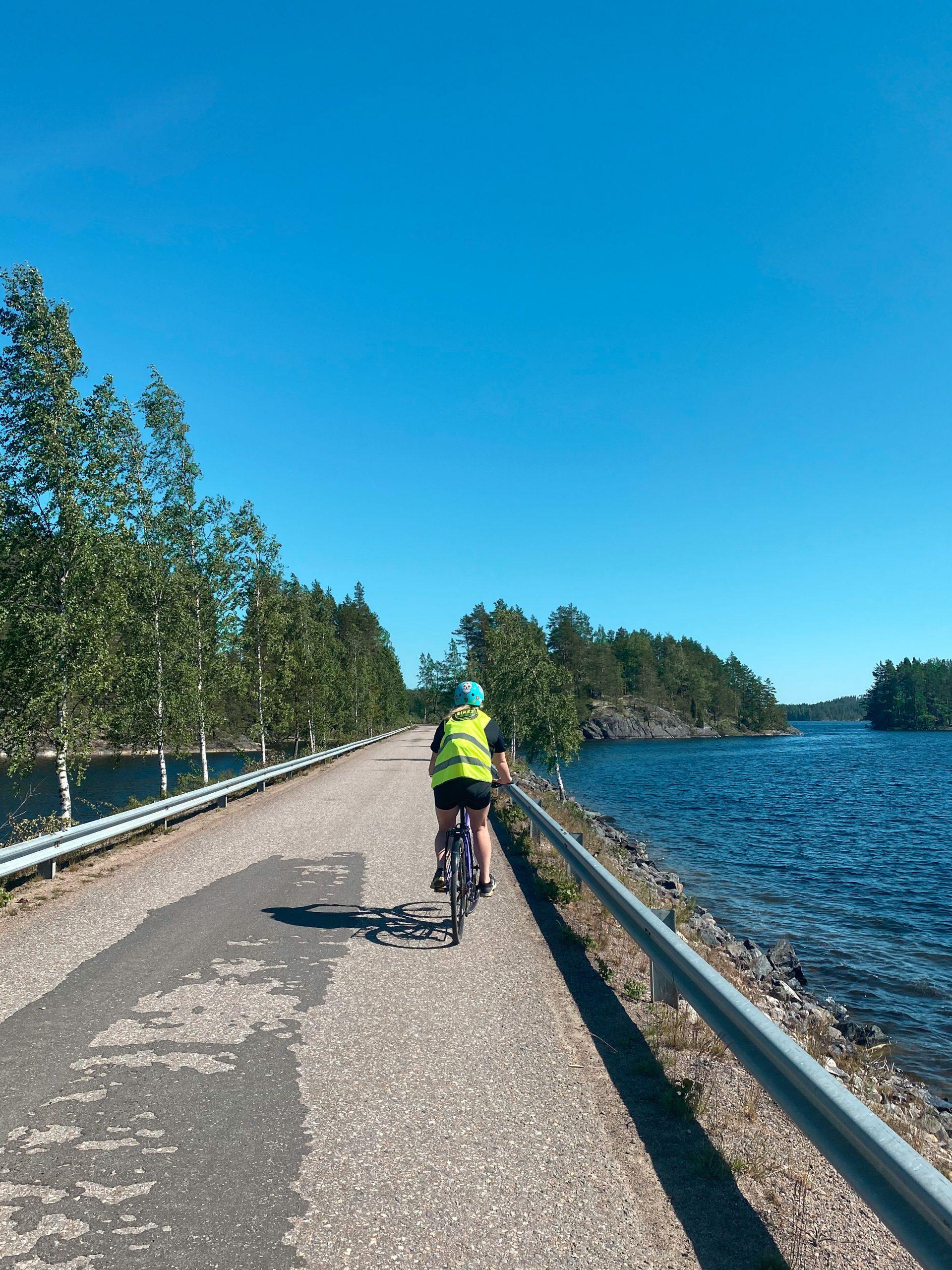 Pyöräilijä Puumalan saaristoreitillä, järvi tien molemmalla puolella
