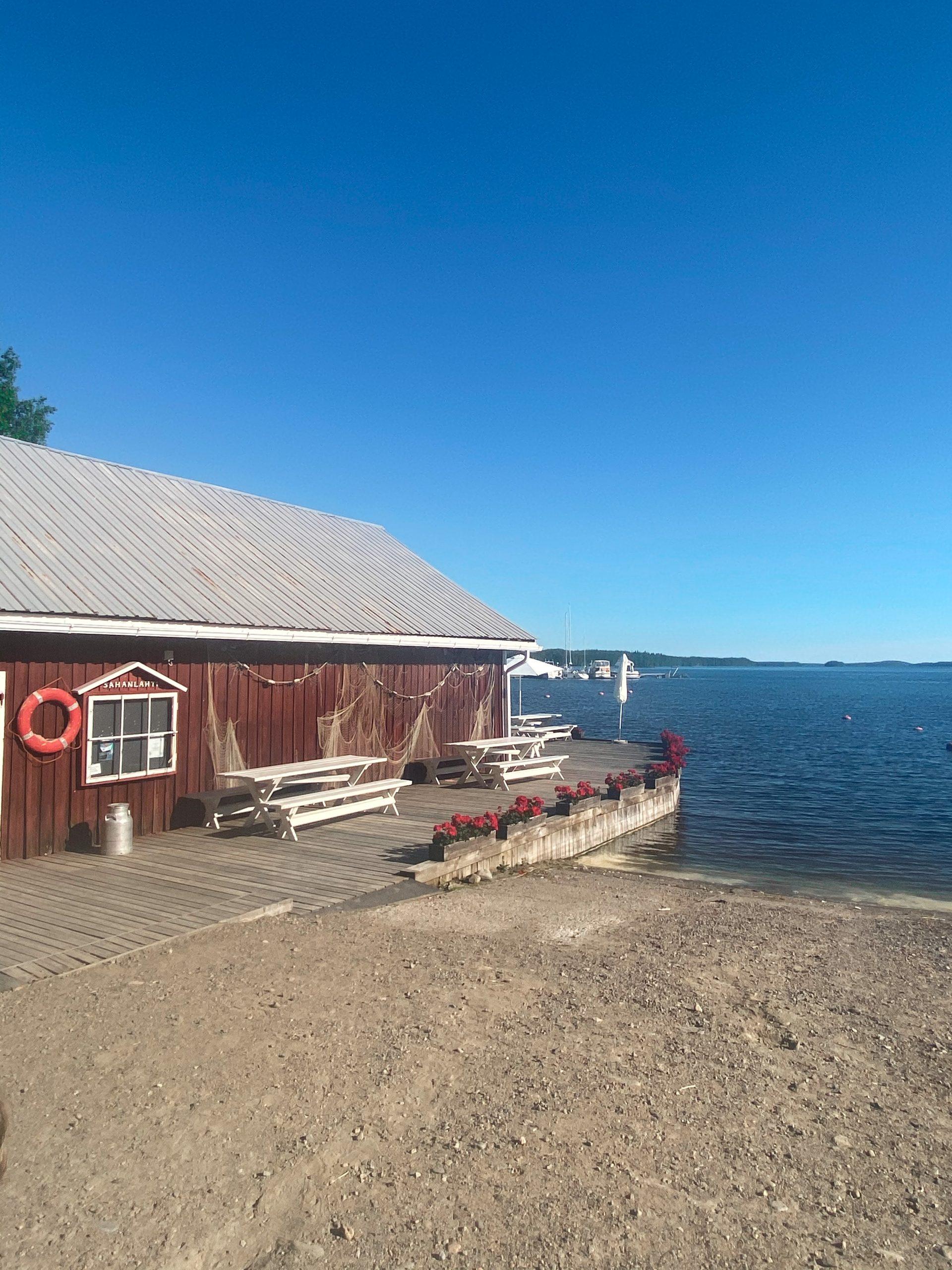 Punainen puutalo ja terassi järven rannassa