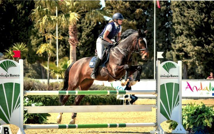 Nainen hevosen selässä hyppäämässä esteen yli