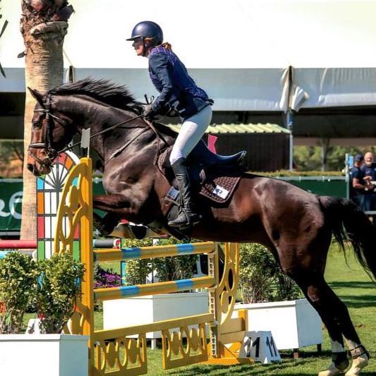 Nainen hevosen selässä hyppäämässä estettä